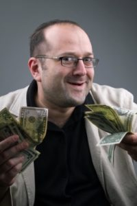 picture of a typical scammer, waving wads of money, giving the false impression that money can be made in a get-rich-quick scam