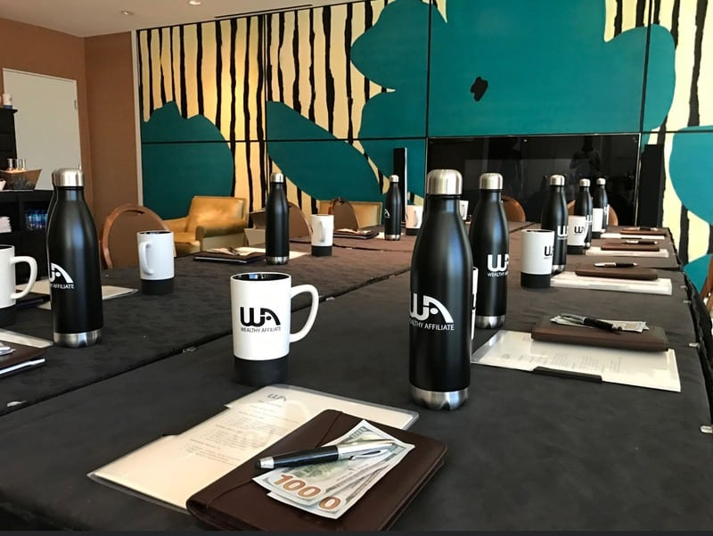 Wealthy Affiliate Review 2020 - Picture from The Wealthy Affiliate Super Affiliate Conference with branded water bottle, mugs and dollars