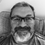 black and white portrait photo of dave o'hara, with glasses and beard